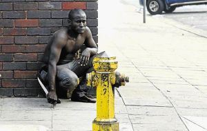 KNIFE EDGE: An immigrant waits for gangs of locals that attacked foreign shop owners in the Durban city centre yesterday. At least three people were stabbed and one burnt. Image by: TEBOGO LETSIE